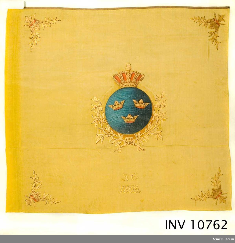 """Fana, Stockholms Borgerskaps Infanterikår, 3 kompaniet. Grupp B.  Fanan är ej beskriven hos Cederström. Duk av gult tvåskaftat siden (taft) med målade emblem: I mitten på ena sidan S:t Erik i profil t v i rund sköld, krönt av sluten kunglig krona. På andra sidan: lilla riksvapnet, tre kronor i rund, blå, sköld under liknande krona. I hörnen korslagda lagerkvistar samt däröver öppna kronor med rött foder.  Bär på inskription. Allt målat i guld med skuggning i sepia. Fäst med förgyllda spikar på guldband, enkel guldfrans upptill och nedtill kring stången. Stång av furu och brunfernissad.   Spets av förgylld mässing. Runda riksvapnet med """"tre kronor"""" inom lyra av lagerkvistar, upptill nordstjärnan inom strålkrans."""