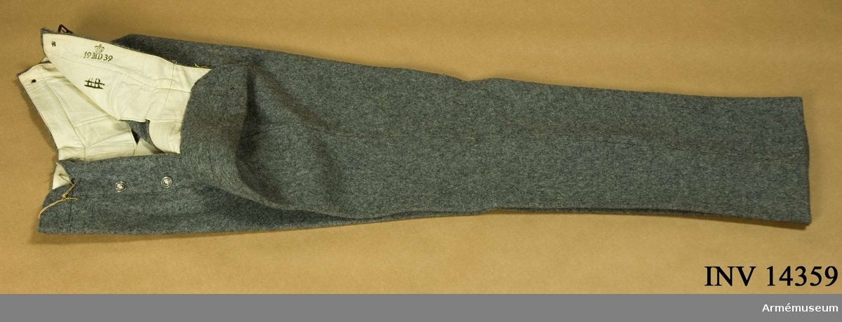 """Grupp C I. Da bukser. Av grått kläde. Två fickor på sidan och på baksidan spänntamp av kläde m spänne. Järnknappar, 3 st på sprund, 6 f hängslen. Foder av vitt tyg m stämpel: krona """"19 M.D. 39"""" (MD= munderingsdepot), """"6 R"""" =6:e regementet. Enl papperslapp från Töjhusmuseet tillhör byxan """"Dyrelaegekorps, menig, uniform m/1915"""". LITT Handbuch der Uniformkunde, Prof. R, Knötel-Sieg, Hamburg 1937, sida 142: Under världskrigets lopp 1914-17 infördes i danska armén uniform av stengrått kläde.Enl Granberg 1951."""