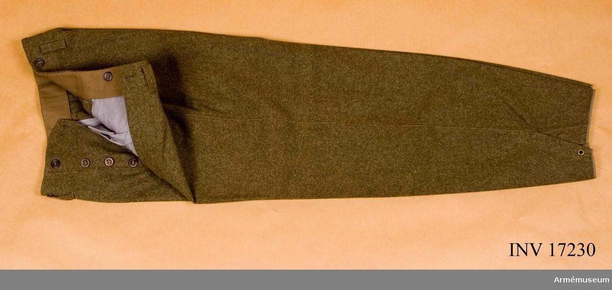 """Grupp C I. BYXOR av Svenska Arméns modell 1939 av svenskt militärtyg.  Byxorna är långa för att användes med pjäxor. Byxorna har en etikett med bilden av en springande hund och """"96"""". På fodret finns en stämpel med """"1940"""", """"96""""."""