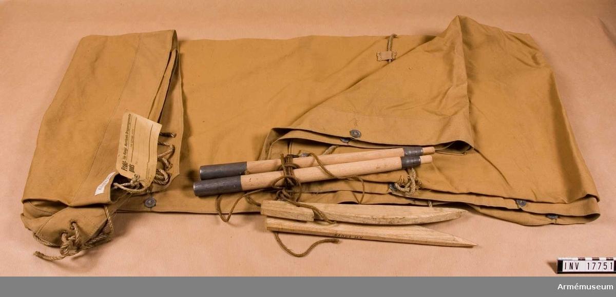 """Av ljusbrunt tyg, ljus khakifärg, 160x160 cm. På tre sidor finns fast sydda järnknappar <sju på varje> och knapphål. På tältbitens baksida finns lika många knappar med påskriften: """"Equipents Militaires"""".  I vart hörn finns två hål, som tjänar till att koppla samman tältdelarna med rep. I mitten och på ena sidan finns rep, fastknutna vid tältdelen.  På tältet finns en stämpel:""""7. 2. 42"""". Tillbehör: 1) två träpålar med hål för rep, 2) två trästolpar med järnförstärkning i båda ändar. I varje stolpe finns en inborrad fördjupning."""