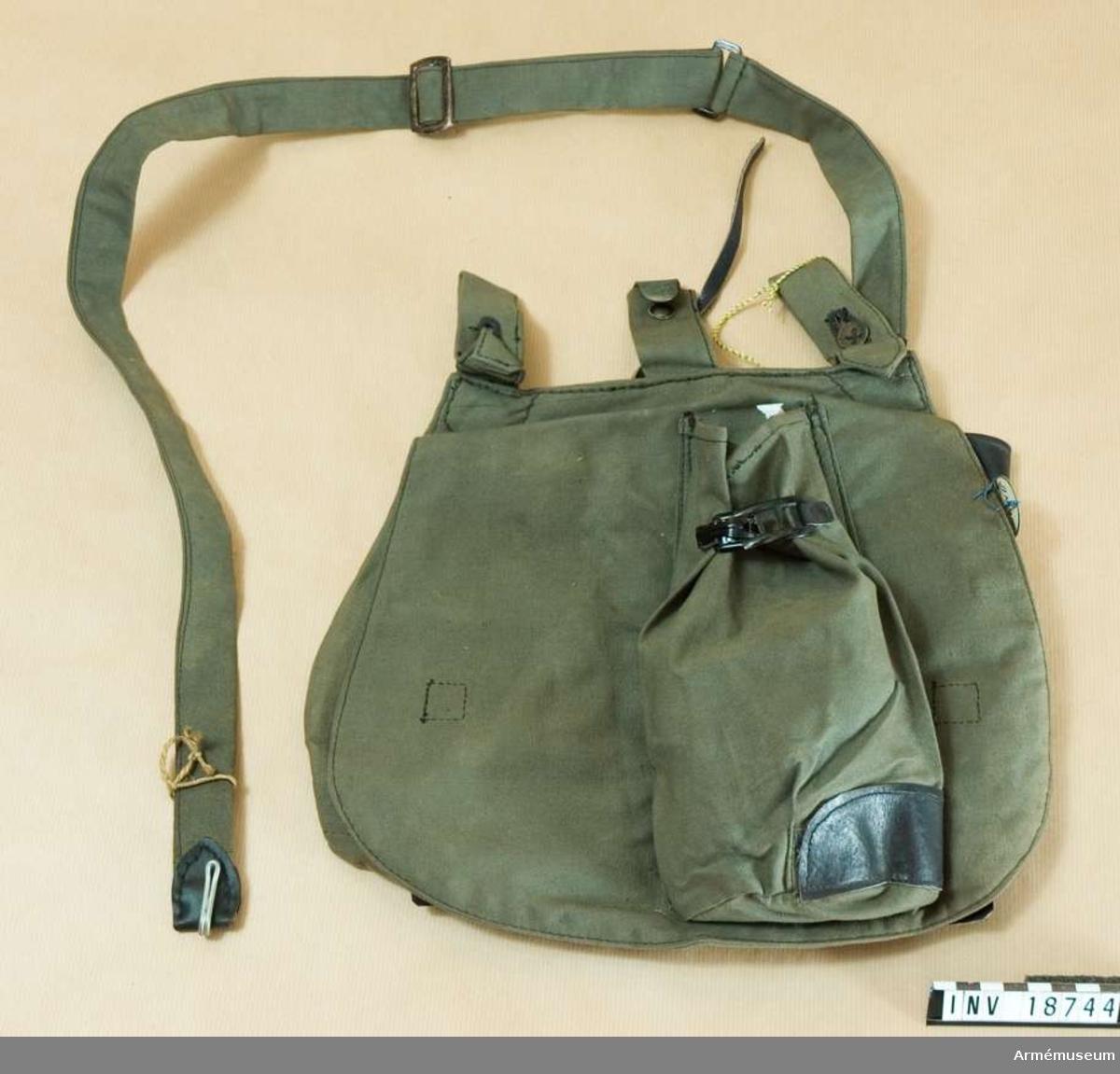 """Grupp C II Brödväska för menig, Holland. 1917. (Brotbeutel) av mörkgrått,tjockt tyg med två hylsor som stänges med knappar och krok för att hänga väskan på bältet. På framsidan finns en ficka som stängs med sölja. På väskans inre sida finns en ficka av svart läder med lock som stängs med knapp och en stämpel """"G.M. 1917"""". För att stänga väskan finns inuti två svarta läderremmar och  två knappar. Väskan har axelgehäng av samma tyg med ring och spänne."""
