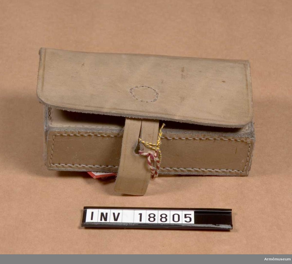 """Av kakifärgat läder. Väskan består av: lock som stänges med en rem med knapphål. Väska: på utsidans nedre del för knäppning; på väskans baksida är en ögla i form av en krok av plåtjärn för livrem. I väskan finns låda av plåtjärn med 1 mellanvägg i varje två avdelningar för 20 patroner. Pappersetikett med text """"Patronväska m/1891 för specialtrupper. Italien"""""""
