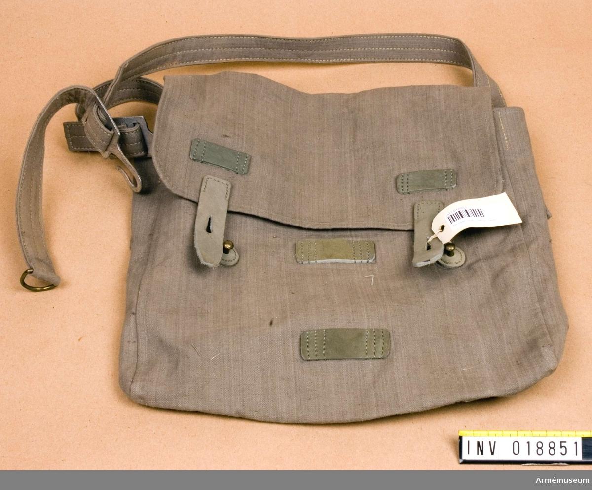 Grupp C II Brödväska av ljust kakifärgat tjockt, impregnerat bomullstyg. Lock som stänges med två remmar och knappar är fastsydda på väskan. På båda sidor fastsydda axelgehänget med två metallhakar och ring. På väskans nedre kant finns två fastsydda spännen.