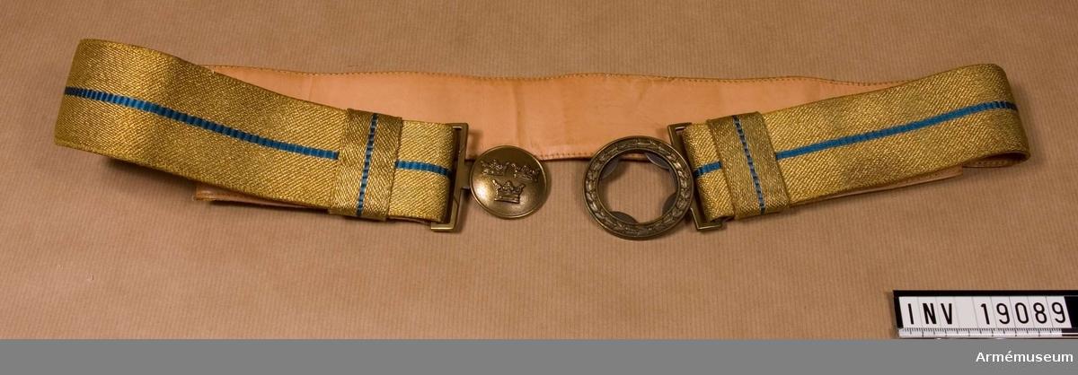 Bandet är vävt i metallfärg 1952 med en blå rand på mitten och  med spänne m/1939. Fodrat med ljust skinn och har två löpare med smal blå silkesrand. Spännet är märkt Sporrong.Används till högtid, parad.