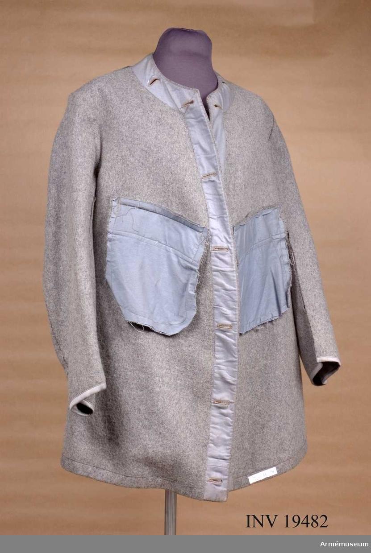 M7379-141000-7. Tillverkad av polyuretabelagd polyamidtrikå. Den 3/4-långa jackan har tryckknappsknäppning och fast huva som kan gömmas i kragen. Jackan är märkt med trekronorsstämpel och tillverkningsåret 1989 i Portugal. Storleken skall passa till en person 180 cm lång och 75 kg vikt.