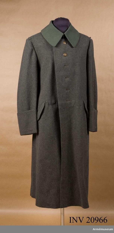 """Grupp C I. Överrock av grått kläde, enradig med 6 knappar. Baktill en slejf som består av två delar, en har två knapphål och hake. den andra sprund med fyra gröna knappar. Axlarna på varje axel en fastsydd knapp och en axelslejf av överrockskläde. Fickor två snedställda sidofickor med halvrunda ficklock. Foder av vitt tyg med stämpel på V sida """"Schneider-Zwangs- Innons"""", """"42 50 124 64"""" i kvadrat med """"98"""" i mitten =  överrockens mått. """"K.R.A.G"""" 1917. Fodret har en innerficka. Knappar är alla flata vävda av metall till och med bak med krona, d:20 mm. Krage, dubbel nedvikt, av grönt kläde andra slag med två hyskor och hakar. Under kragen finns en slejf på kragens vänstra sida med två knappar.  Ärmuppslag rundskurna av överrockens kläde 16 cm höga. LITT  Die Deutsche armée in ihren neuen Feld- und Friedens- uniformen. S 1,7. Denna mantel infördes i tyska armén efter en dagorder av den 21 september 1915 för meniga vid alla vapenslag med krage av särskilt kläde hela tyska armén fick detta år ny fältgrå uniform. P Cassberg, Deutschlands Armée in feldgrauer Kriegs- und Friedensuniform. Sidan 9. Överrock mantel beskrivning. Ritning av överrock från fram och baksida. Överrocken har en pappers- etikett med texten: """"Nachprobe. Das feldgrauen Mantel für alle waffenzattungen. Zu Nr 381. 10.15.   B 3 D II Aug. Bekleidungs- amt des Gardeskorps. Nebelung und Vorster und?Enl Granberg."""