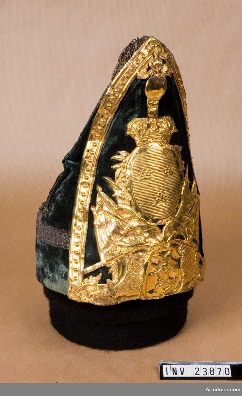 Grupp C I. Ur uniform för underofficer vid Södermanlands regemente 1765-79. Består av rock, väst, knäbyxor, grenadjärsmössa, skor, handskar, dammasker, mässingsspänne, skjorta. Ev. officersmössa. Av grön sammet med förgylld vapenplåt och kantad med guldsnören. PUBL  AMV Medd X, s 68.