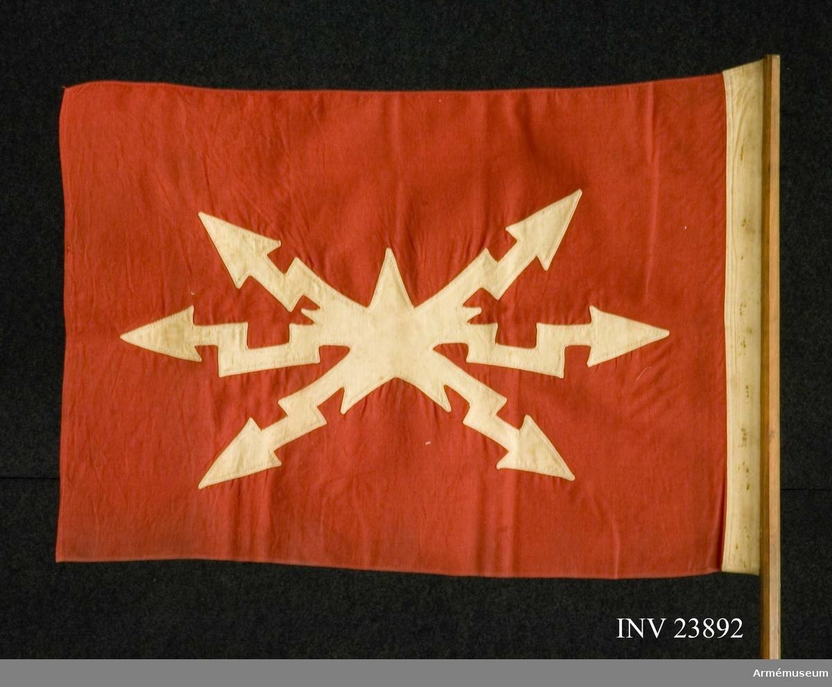 Samhörande nr är 23890-6, riktflaggor, fodral. Grupp H III. Duken är röd, kypertvävd, förmodligen av ylle (chalon?) med fälttelegrsfkårens vingförsedda kompanimärke i vitt infällt. Vit kant ca 4 cm löper längs dukens sida parallellt med stången. Duken är monterad på en 8-fasad käpp som smalnar av upptill - först fäst med spikar i en läderrem och därefter i stången.