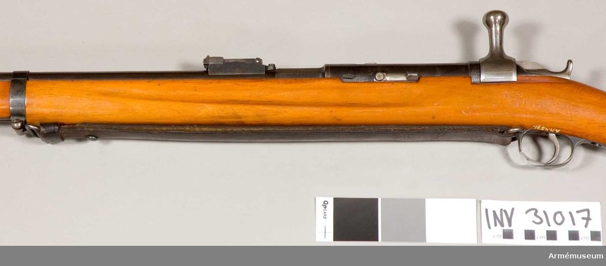 Samhörande nr 31015-7, gevär, mynningsskydd, gevärsrem. Jarmann. Grupp E II. Remmen är av svart läder och har en knapp av järn. Bilaga: Generalfälttygmästareexpeditionen 1906-11-30 dnr 1686.