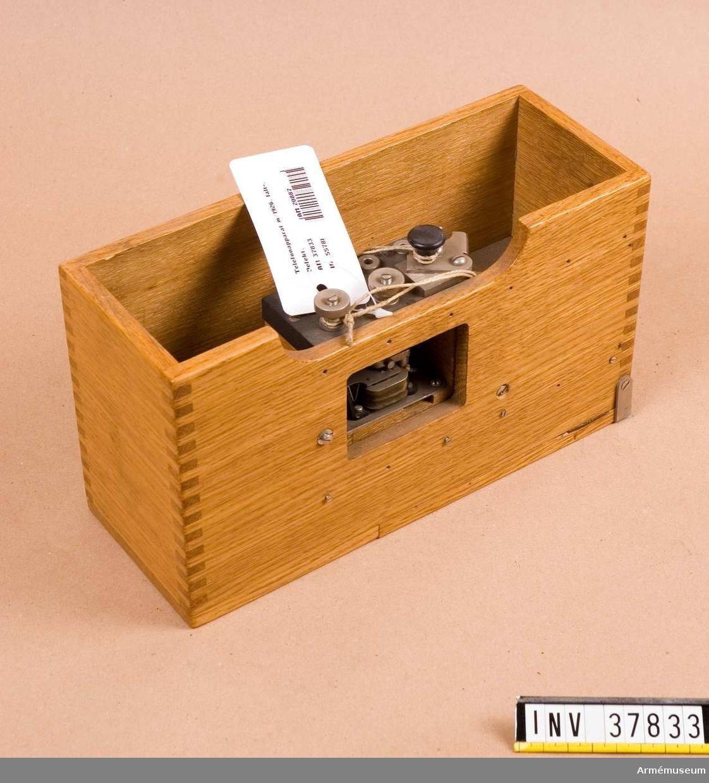 Grupp H I.  Apparatlåda av eketrä med delvist innehåll. Saknas: metallplats som täcker rum för vibratorn.  Defekt. Mått: 250x95x145 mm.