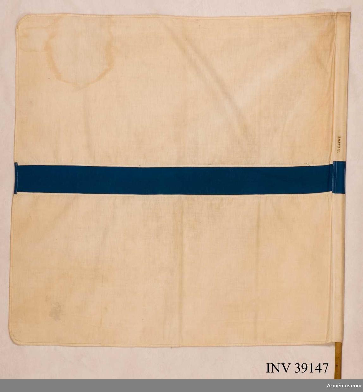 Grupp H III.  Vit flagga med blå rand från stången mot kortsidan, 8 cm bred.Enligt GK 1981.  Samhörande nr AM.039147-AM.039148, signalflagga, käpp.