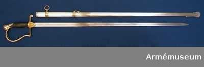 """Grupp D II Baljan är av förnicklat järn och har ett litet munbleck samt två 14 mm. breda beslag, som på mitten har en bred, upphöjd, slät rand, men vilka ovanför och nedanför denna rand är prydda med ett par smala, av ett på mitten försänkt fält skilda åsar. Det övre av dessa beslag har på ryggsidan en ögla, vari en rörlig koppaelring är fäst, och från ryggsidan av det nedre beslaget går en för sabelstödremmen avsedd bygel först rakt bakåt, så snett nedåt till baljans rygg. Munblecket, beslagen, koppelringen och stödremsbygeln är av förgylld brons.OBS. I generalorder no.1120 den 8 november 1889 påbjuds, att styckjunkare skullle ha samma slags sabel som artillerioffi- cerarna, men baljan skulle ha """"band med tillhörande ring och bygel av stål. Fästet på sergeantsablarna m/1889 (modell fastställd i samma generalorder) skulle ha oförgyllt fäste av rödgul metall samt klinga och ballja av smma typ som styckjunkarna. Bandet på bägge typrna ändrades senare enligt generalorden av 1899 till likhet med bärinrättningen på 1899 års infanterofficerssabel. PUBL  AMV Med. XVI s. 61 (fästet).  Samhörande nr är AM.39926-7"""