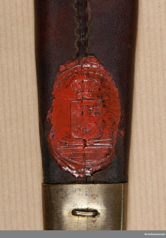 Grupp D II. Baljan är klädd med brunt läder och har doppsko samt med koppelhake försett munbleck av mässing. På baljans insida finns upp- och nedtill på lädret Generalfälttygmästareämbetets sigill i rött lack. På insidan av doppskons spets sitter en kronstämpel.
