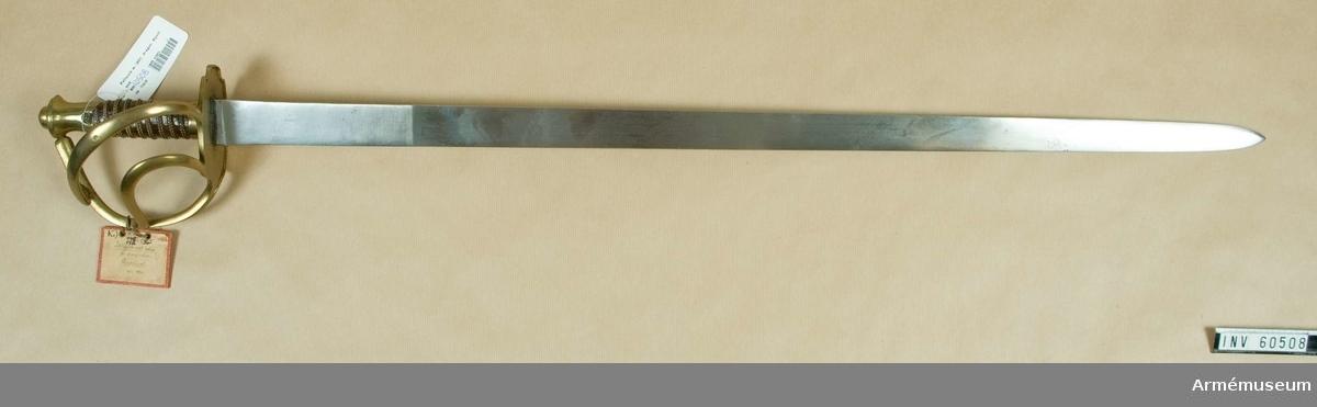 Grupp D II.  Klingans bredd upptill är 39 mm.Klingan är rak och till större delen av sin längd eneggad med  kilformigt tvärsnitt, men närmast udden är den på en sträcka av  omkring 165 mm slipad med egg även på ryggsidan.  Upptill på  kvartsidan finns en stämpel. Fästets beslag är av mässing.  Kaveln är klädd med skinn, som  ursprungligen tycks ha varit brunt. Kring kavelns fria del går  en spiralräffla 9 varv.  I botten på denna räffla är två  mässingstrådar anbringade.  Vardera tråd är hopsnodd av två  parter, men den ena tråden är vänster-, den andra högersnodd.   Längst ned omges kaveln av ett ringliknande, omkring 14 mm brett  mässingsbeslag.  Kappan bildar upptill en på sidorna med  horisontala ränder prydd knapp, på vars översida finns en ganska  stor, oval, avrundad nitknapp.  Kappans nedre del bildar en sorts  nedåt, vidare holk, som på ters- och kvartsidan har en från  nederkanten utgående trekantig urtagning, vars spets fortsätts av en vidare, cirkelformig urtagning.  Parerplåten är rätt stor och har svagt förstärkta kanter på undersidan. Den har närmast formen av en långdragen oval, dock baktill med en liten halvrund urtagning både på ters- och på kvartsidan samt framtill med en motsvarande urtagning på var sida om handbygeln.  Den sistnämnda utgår från parerplåtens främre kant, är framtill kälad och  baktill halvrund samt går i båge till kappan, i vilken framtill finns ett hål, där handbygelns övre ände är instucken.  På terssidan utgår ungefär från mitten av parerplåtens kant, en flat, på mitten bredare, S-formig spång, som går till handbygeln, vilken den träffar vid bygelns övre krök. Ungefär mitt emellan det ställe, där denna spång och det, där handbygeln  utgår från parerplåten, utgår på terssidan från parerplåtens  kant ännu en S-formig spång, fullkomligt lik den förstnämnda,  vilken träffar handbygeln på mitten.  Ungefär på mitten av den  förstnämnda spången finns en stämpel med två bokstäver, och  baktill vid kanten på parerplåtens övre sida är s
