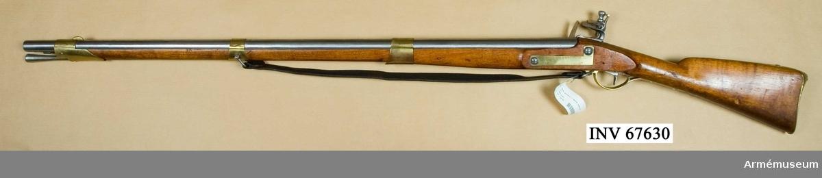 """Består av: 1 gevär, 1 gevärsrem av läder.Låset märkt """"CS"""", pipan märkt """"AT PG S"""". Pipor från div äldre svenska gevär, som ändrats till likhet med 1815 års pipor. Lås från diverse äldre svenska och utländska gevär, som om så behövdes försetts med varhake. I övrigt som 1815 års gevär. kal 20 mm. Tnr 26."""
