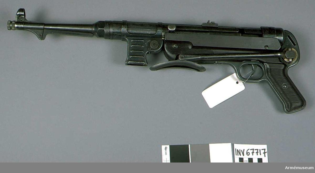 """Kaliber 9 mm, tillverkningsnr 59931. Märkt M.P.40 bnz. 42. """"Tysk örn"""". Konstruktionsprincip: tungt slutstycke. Hel längd 840 mm, med kolven infälld 640 mm. Bestående av 1 st kulsprutepistol, 1 st gevärsrem av läder, märkt L & F.1986-09-30 Märkt """"GG"""" ? """"3 59931 993"""" örn """"WsA 23"""" (under)."""