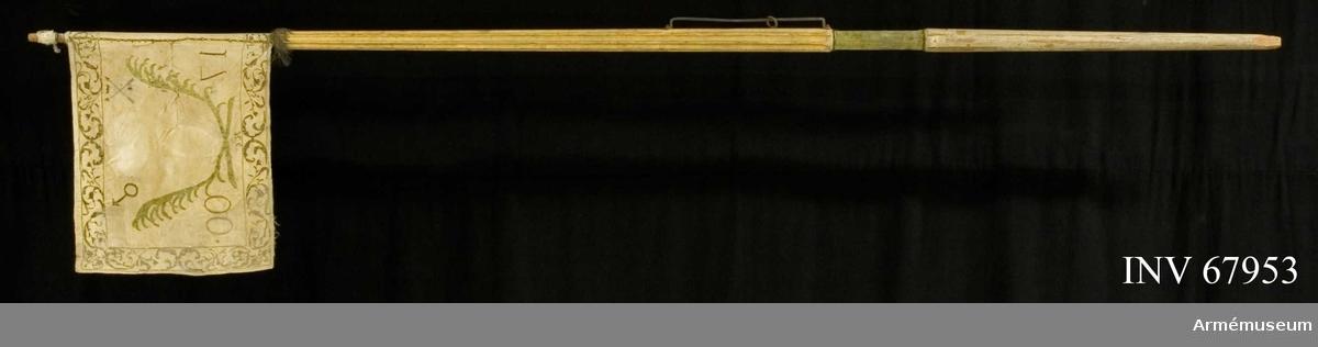 """Duk: Enkel, tillverkad av vit sidenatlas. Duken fäst vid stången med två rader tennlickor på smalt guldband.  Dekor:  På tre sidor en bård bestående av silverbroderade lagerkvistar med läggsöm i grönt, lika på båda sidor, i inre hörnet """"17"""" och i yttre """"00"""" i silver samt i inre, övre hörnet Dalarnas vapen krönt med öppen krona, två korslagda pilar i silver (?) dubbelt C under sluten krona i applikation (Karl XII:s namnchiffer). Mot nedre delen finns en signatur. I yttre övre hörnet den astrologiska symbolen för Mars, samma symbol som används för järn.  Frans:  Endast resterna av en silverfrans.  Banderoller: Tofsar och snodd av vitt silke och silver.  Stång: Tillverkad av trä, kanellerad, övre delen förgylld, nedre delen är målad i gråvitt. Ljusgrön sammet påsatt med smalt guld (?)- band och spikar."""