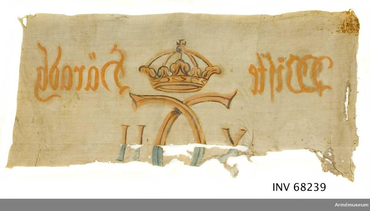 """Uppbådsfana, Wiste (?) härad.  Samhörande med stång nr 17335.  Horisontell skarv . Vertikal skarv som """"delar"""" duken i 2 delar, 500 mm resp. 1170 mm långa. Nedre dukskarven målad i blått. Övre delen av ockramålad linnelärft.  Dekor: Målad endast från dukens insida, Karl XII:s namnchiffer, dubbelt C med X-II på ömse sidor, krönt med sluten krona, på det övre fältet i gult och brunt på det nedre i blått och svart. *Text på ömse sidor om chiffret, upptill i gult och nedtill i svart. Under detta text i svart.* På ömse sidor om chiffret upptill i gult: """"Wiste häradh"""" .Under detta i svart: """"A° 1710""""."""