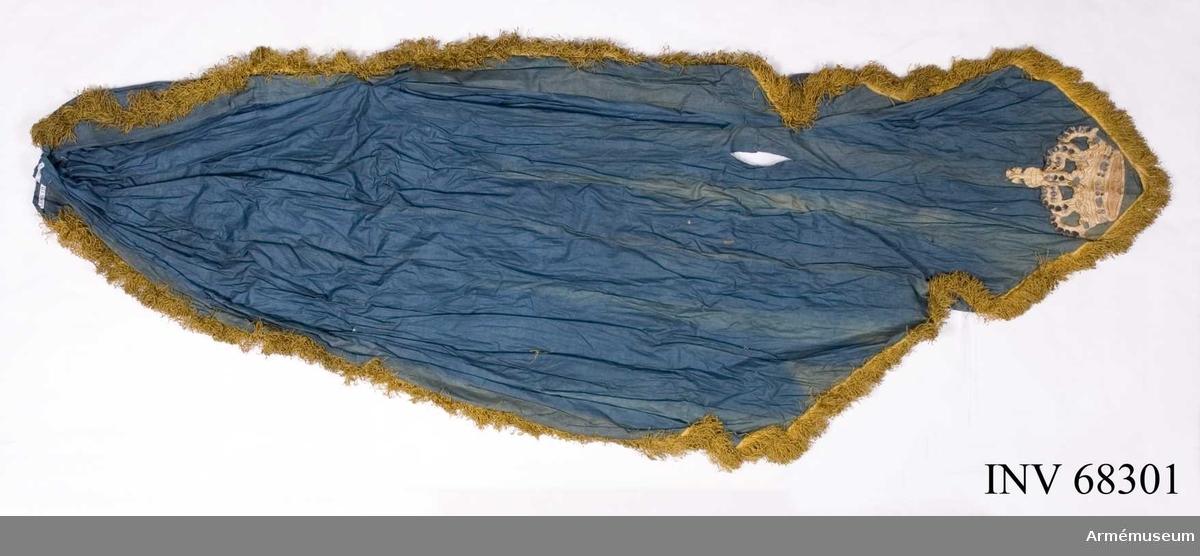 Fanduk av blå bomullslärft med gul silkesfrans runt ytterkanterna och nedtill i spetsen en applicerad, broderad krona i övervägande silke - sannolikt överflyttad från något liknande föremål.