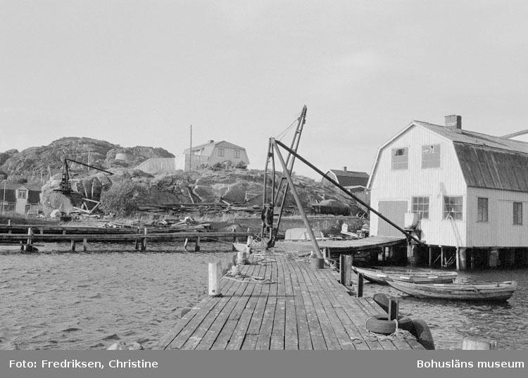 """Motivbeskrivning: """"Tommas Löfberg, på bilden syns f.d mekanisk verkstad. Mitt i bild på berget syns varvsägarens bostad."""" Datum: 19801008"""