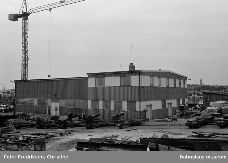 """Motivbeskrivning: """"Amigo varvet, Öckerö. På bilden syns senaste tillbyggnaden vid varvet (1977), där inredningsarbeten utförs""""."""