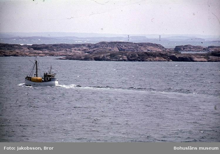 """""""Inseglingsfyrarna till Scanraff långt borta. Vy med fiskebåt i förgrunden. Fyrarna Dynabrott och Brandskärs Flak""""."""