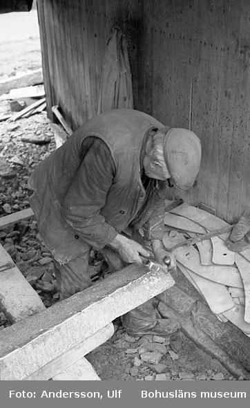 """Bohusläns samhälls- och näringsliv. 2. STENINDUSTRIN. Film: 12  Text som medföljde bilden: """"Arbete med pikmejsel för att få bort ojämnheter. Kantsten bearbetas med pikmejsel och """"fejsel""""´(=handslägga). Pikmejselns användes för att få bort ojämnheter i stenen. I bakgrunden ses papp- och plywood-mallar för tillv. av radiesten (""""kroksten"""")""""."""