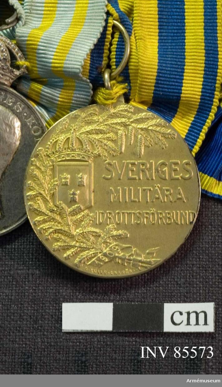 Grupp: M.  Medaljen saknar ytterrand, har överst en fast diameter 33 mm ögla för bandhållaren. Åtsidan: Å mittpartiet till högeri relief: SVERIGES MILITÄRA IDROTTSFÖRBUND, i avtagande storlek på 3 rader. Till venster därom, likaledes i mitten av rektangulär, nedåt tillspetsad slät sköld med en slät, upphöjd kant och Sveriges tre kronor samt en stor kunglig krona över skölden. Längst till venster, följande medaljens kontur och upptagande 2/3 av dess längd en grankvist med kottar, delvis inlagd på sköldens venstra sida. Nederst en lös bandknut, varå är inpräglat 1909. Nedan för kvisten: S. KULLE. GRAVÖR. På frånsidan synes till venster Svea, seende åt höger, i fotsid dräkt och med hårflätor virade omkring huvudet, håller i högra handen en mot marken stödd spetsig, slät sköld med släta, upphöjda kanter och prydd av Sveriges tre kronor. Den venstra armen är framsträckt, och handen håller en lagerkvist. I medaljens mitt läses i inpräglade bokstäver: KAPTEN K.A.B. AMUNDSON 1911 på 3 rader. Vid Sveas fot tallkvistar. Nederst  V. CARLBERG P.  Bandet gult med 4 mellanblå ränder, 2 bredare innerst och 2 smalare utåt. Beskr. Prn.  Förvaras: på nål tillsammans med andra svenska dekorationer, förråd -56.