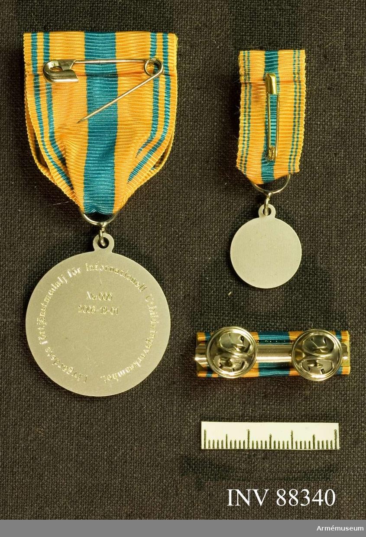 Tre samhörande föremål; en minnesmedalj, en minatyrmedalj och ett släpspänne. Bandet kluvet i gult, blått, gult med två smala blå ränder på varje sida.