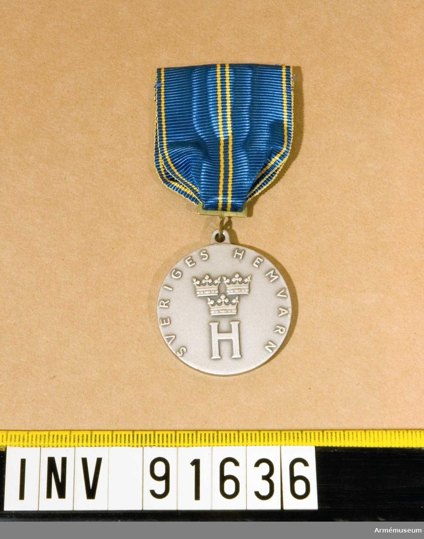 Medalj i silver. HvSM.  Hemvärnets vapen på framsidan och Kraftvärnets vapen på baksidan. Band i blått med två gula streck på mitten och ett gult streck på vardera sidan.