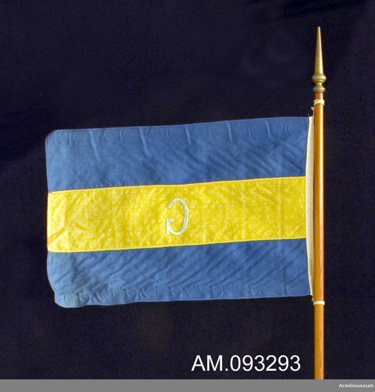 Enkel flagga i linne på trästång med svarvad knopp målad i guld. Utförd av Stockholms flaggfabrik AB.