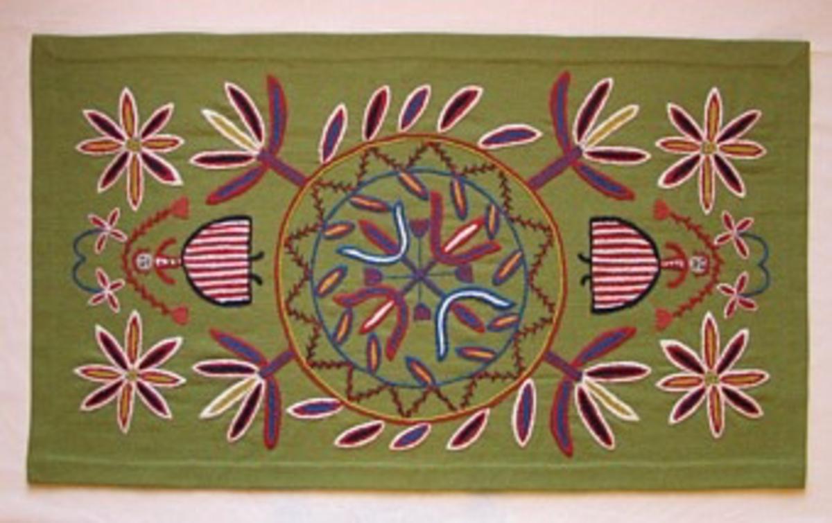 Rektangulär framsida till skånsk åkdyna, broderad på gröngul botten med entrådigt ullgarn dubbelt, i klarblått, rött, naturvitt, gult, mörkblått och naturgrått. Motiv med stor cirkel i mitten, naiv blomkrans med fyra stora blommor ut mot hörnen. En blomma i varje hörn, kvinna med huvudet mot kortsidorna. Fållad med flätsöm. Uppbroderad som icke exakt kopia av original som finns på Länsmuseet i Kristianstad.