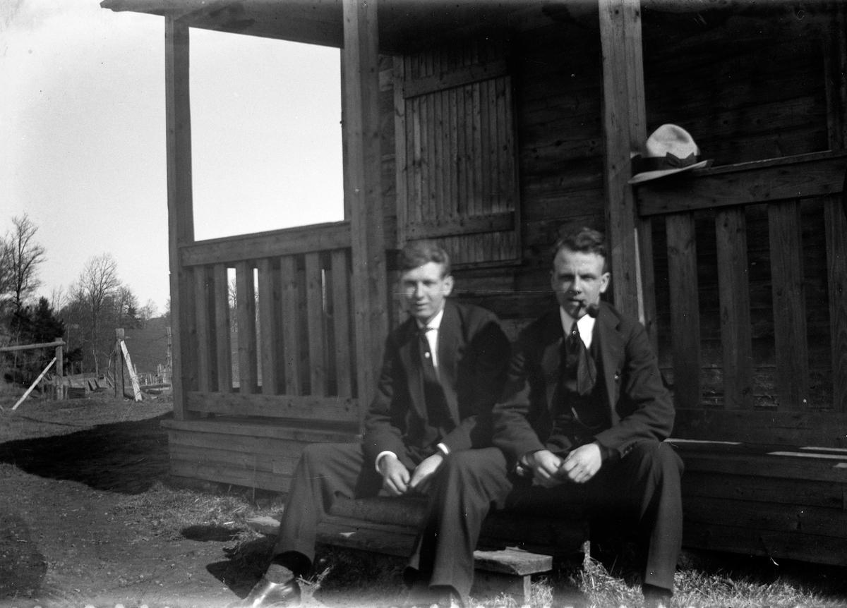 Två män sitter på trappan till husets förstukvist.