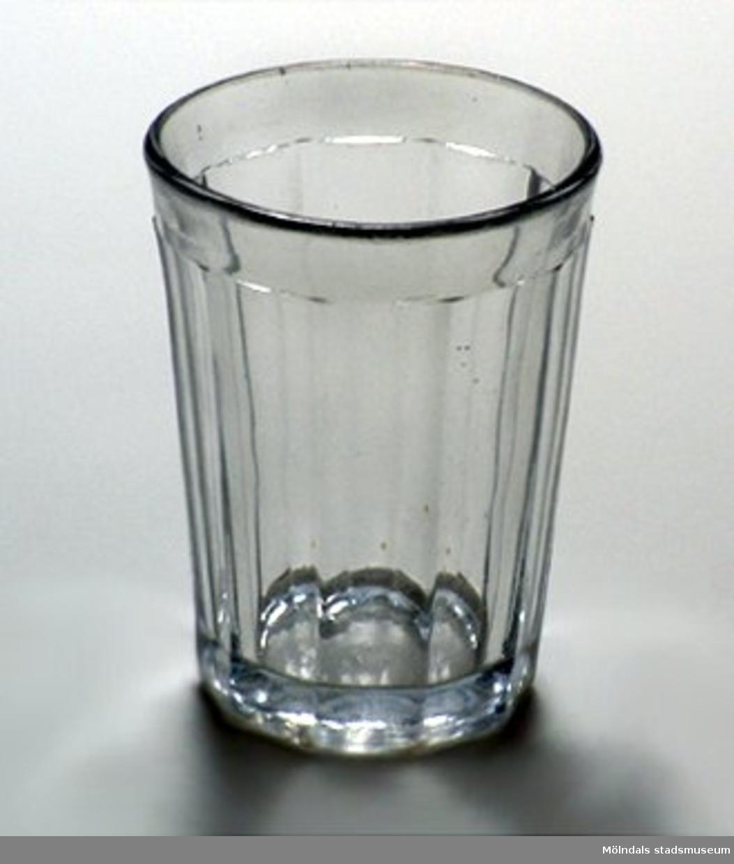 Tjockväggigt glas med starkt urslipad botten. Sidorna har vertikala plana ytor, ca 20 mm breda,  och överkanten har horisontal kant, ca 10 mm bred.