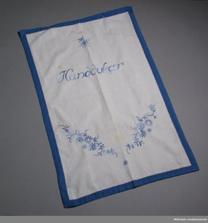 """Vit paradhandduk kantad med blått brett band. Broderad med blå blommor och """"Handdukar"""". Märkt """"HJ"""" i vitt i ena hörnet."""