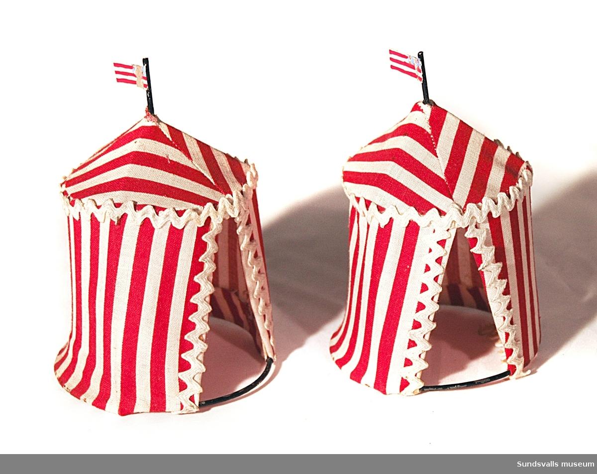 SuM 2776:1-2 leksakstält av vit- och rödrandigt tyg. En flagga av metall som troligtvis ska föreställa den amerikanska flaggan.