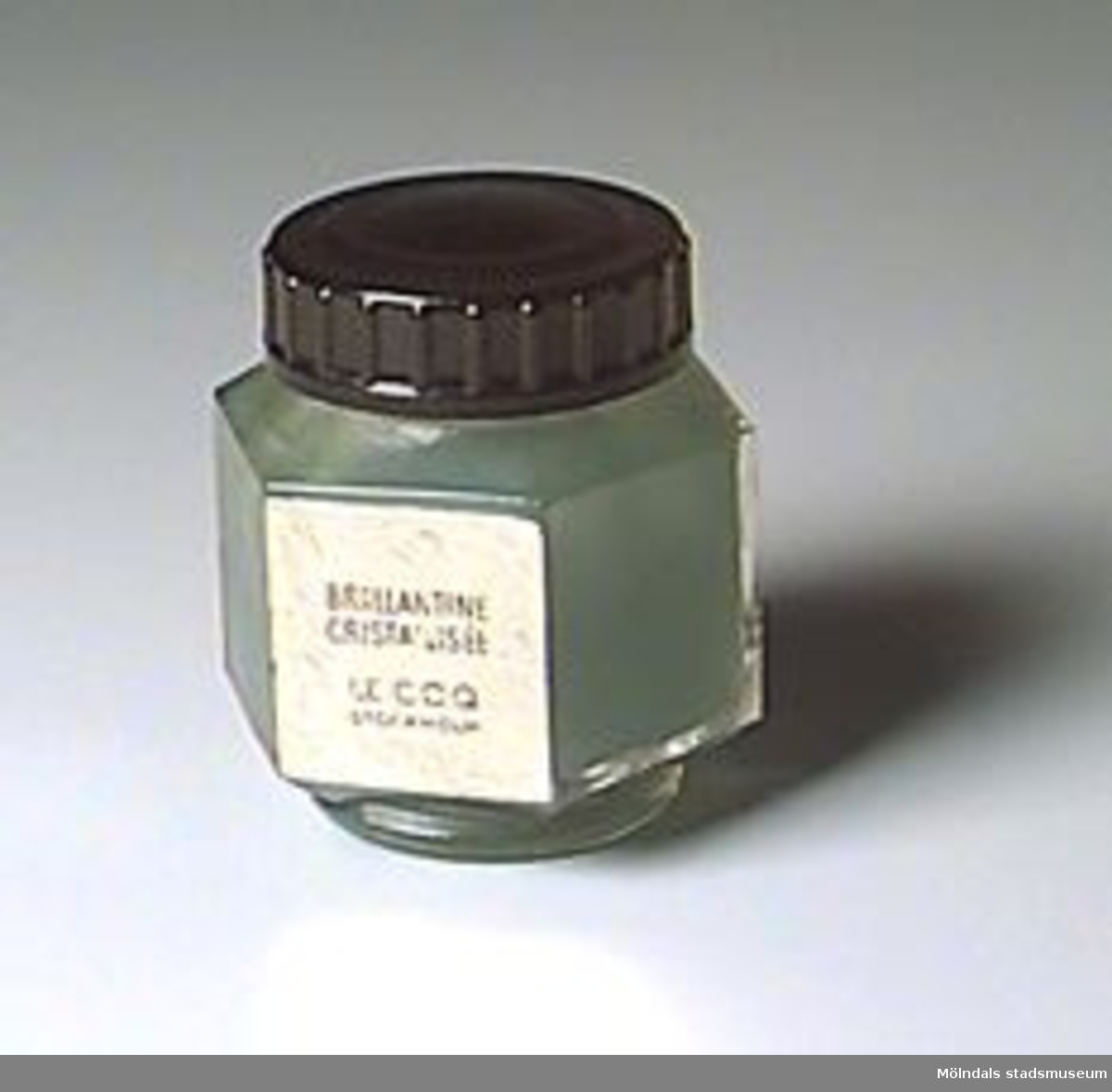 """Sexkantig glasburk med rund fot, svart skruvlock. Innehåller grön pomada. Etikett i guld: """"Brillantine Cristallisée/ Le coq/ Stockholm"""". Pris enligt prislapp: 4,75 kr.Kjellberg arbetade i väveriet på Mölnlycke fabriker 1916-1969."""