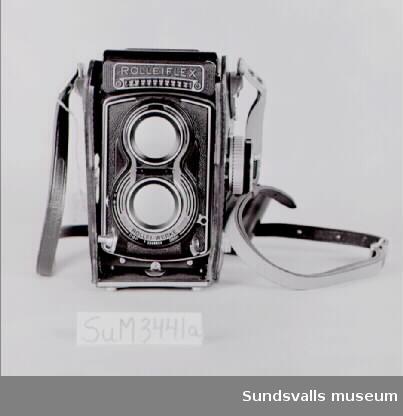 SuM 3441:a-b kamera med väska och tillbehör. Kameran är av märket 'Rolleiflex', en tvåögd spegelreflex kamera med tillverkningsnumret 'T 2246889'. Linserna av märket 'Tessar 1:3,5 f=75 mm' är tillverkade hos Carl Zeiss med nummer '4785573'. Kameran har en exponeringsmätare på sidan och under linserna sitter ett uttag för blixt. Den förvaras i en väska med axelrem och filterhållare i brunt läder fodrat med vinröd textil. SuM 3441:b är en ask i ljusblått och grått papper med texten 'Einbau-Belichtungsmesser Light meter elements Posemètre Fotómetro. Rollei. Rollei-Werke Franke&Heidecke Braunschweig'. Den innehåller tillbehör i form av en extrafront till kameran, en rund platt bricka som fungerar som filmvalsminne, samt en bruksanvinsning till hur man installerar en exponeringsmätare.