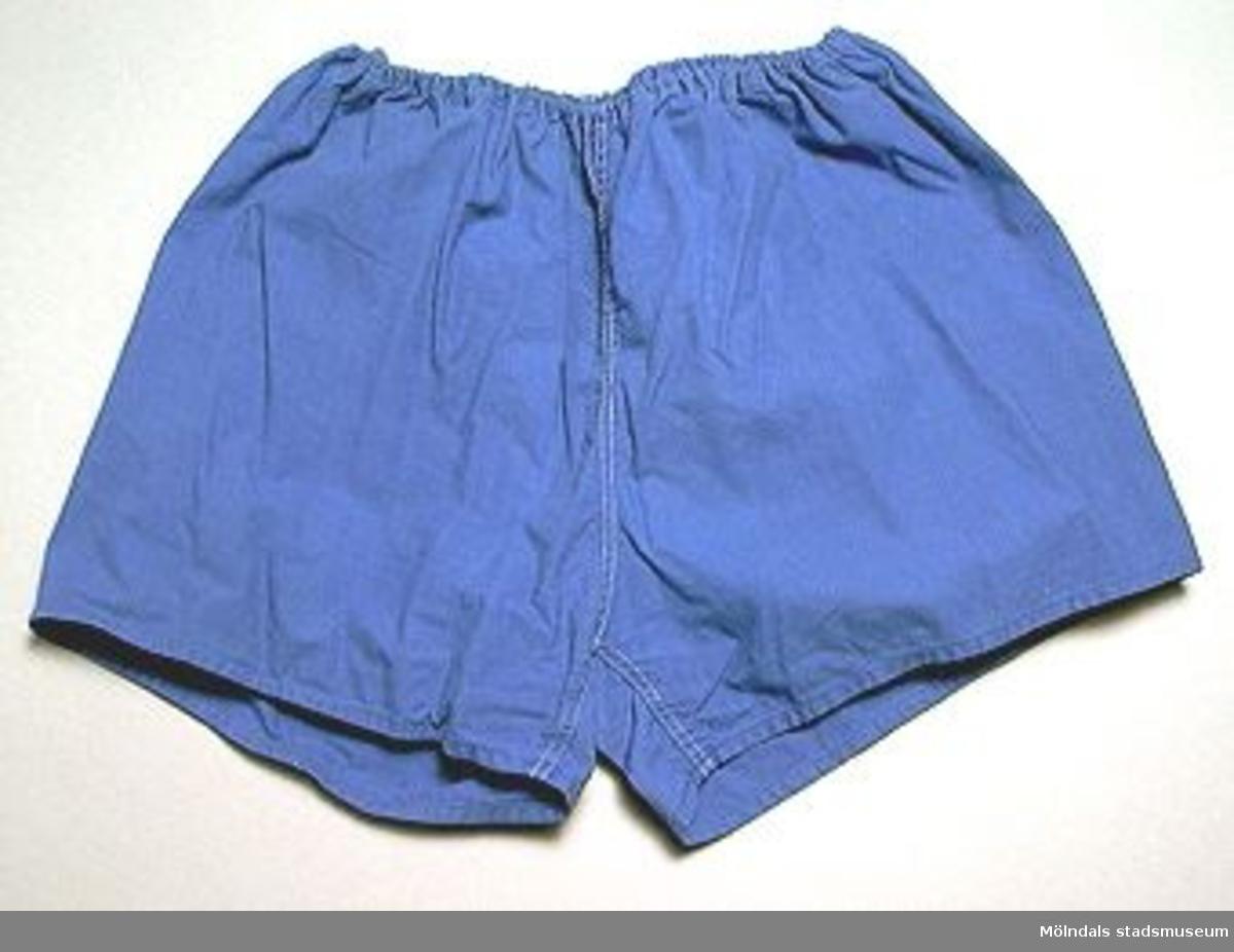 Gymnastikbyxor för herrar. Blå, korta med liten bakficka. Ej gylf. Midjeresår. Användes vid gymnasitk och idrott.