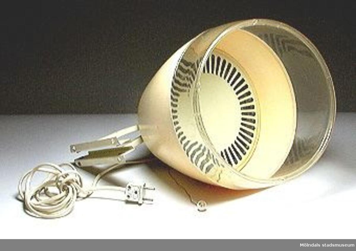Elektrisk hårtork av typen torkhuv med inbyggd fläkt och värmespiral. Av gul plast och med nederdelen transparant. Hållare som kan väggmonteras eller klämmas fast (med skruvkläm som sitter i huvens överdel).Märkt: Magic air, 220v-50-450w G.E.C. Made in England, Type 152.