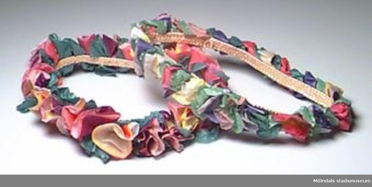 Två stycken kransar med blommor av många färger i silkespapper. Små rundlar av silkespapper har lagts på varandra och veckats ihop. Sedan har de fästs med häftapparat på ett centimeterbrett flätat band i halmarbete. Handgjort.Tidigare sakord: blomsterkrans, papper.Gåva av Katrinebergs daghem.