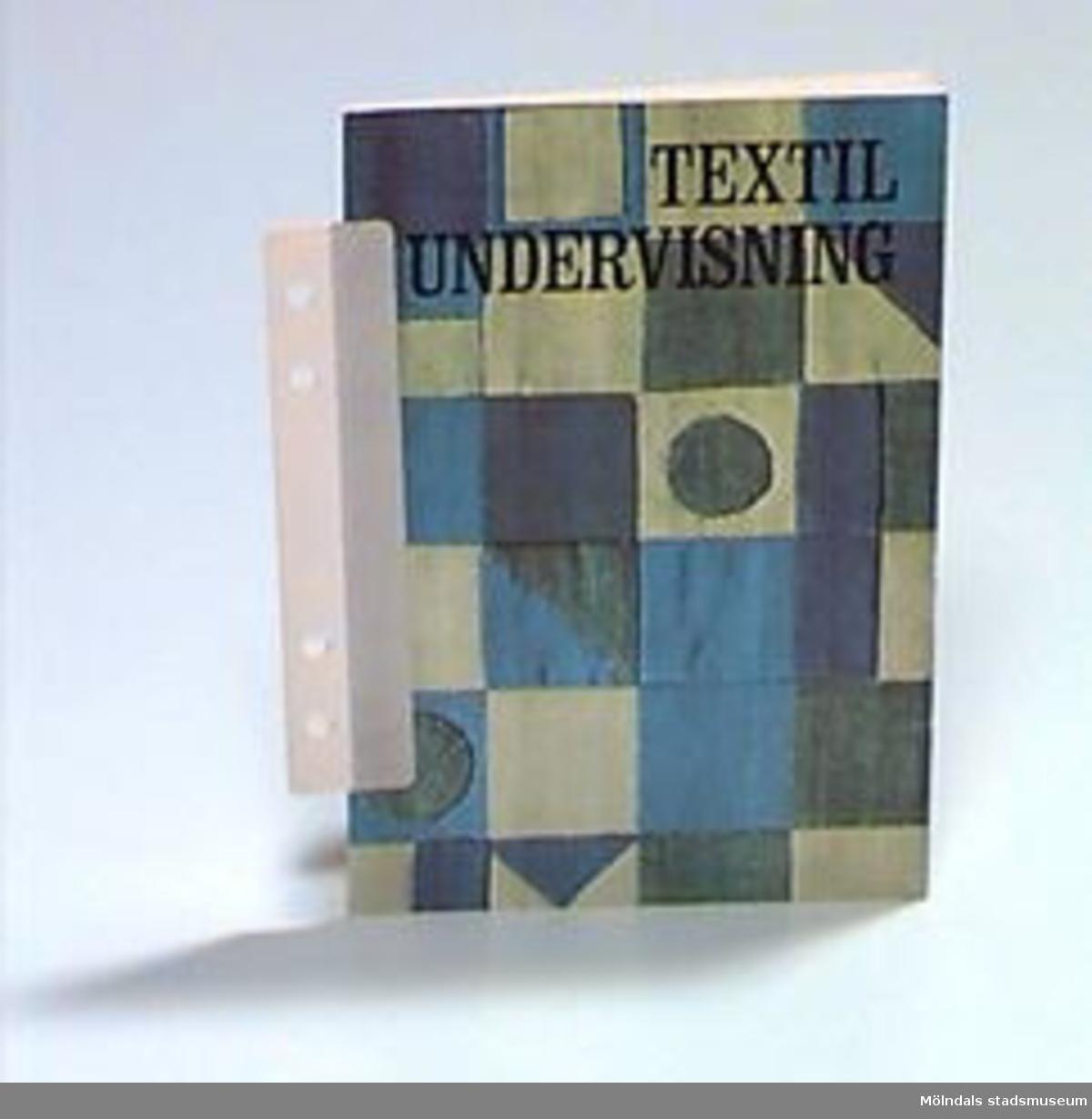 """""""Textilundervisning"""" - ett tunt häfte som beskriver huvudmomenten i textilundervisning. Omslaget är ett fotograferat lappverk i gröna och blå nyanser. Klisterlapp med Birgit Ekstrands namn och adress på insidan av omslaget.I ryggen är två hålslagna pappbitar klistrade för att häftet ska kunna sättas i en pärm.Övriga uppgifter se 02643:1."""