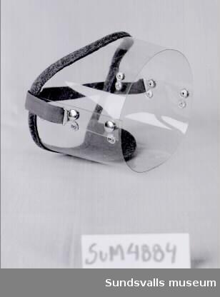 Cylinderformat ansiktsvindskydd för användning vid mopedåkning. Skyddet består av två separata delar som knäpps ihop med tryckknappar. Partiet mot ansiktet är kantat med grönt filttyg och på en flik av filttyget är symbolen 'tre kronor', '1963', samt ordet 'Expace' (?) tryckta i svart. Skyddet hålls fast på huvudet med hjälp av ett grönt resårband, som är reglerbart i längd.
