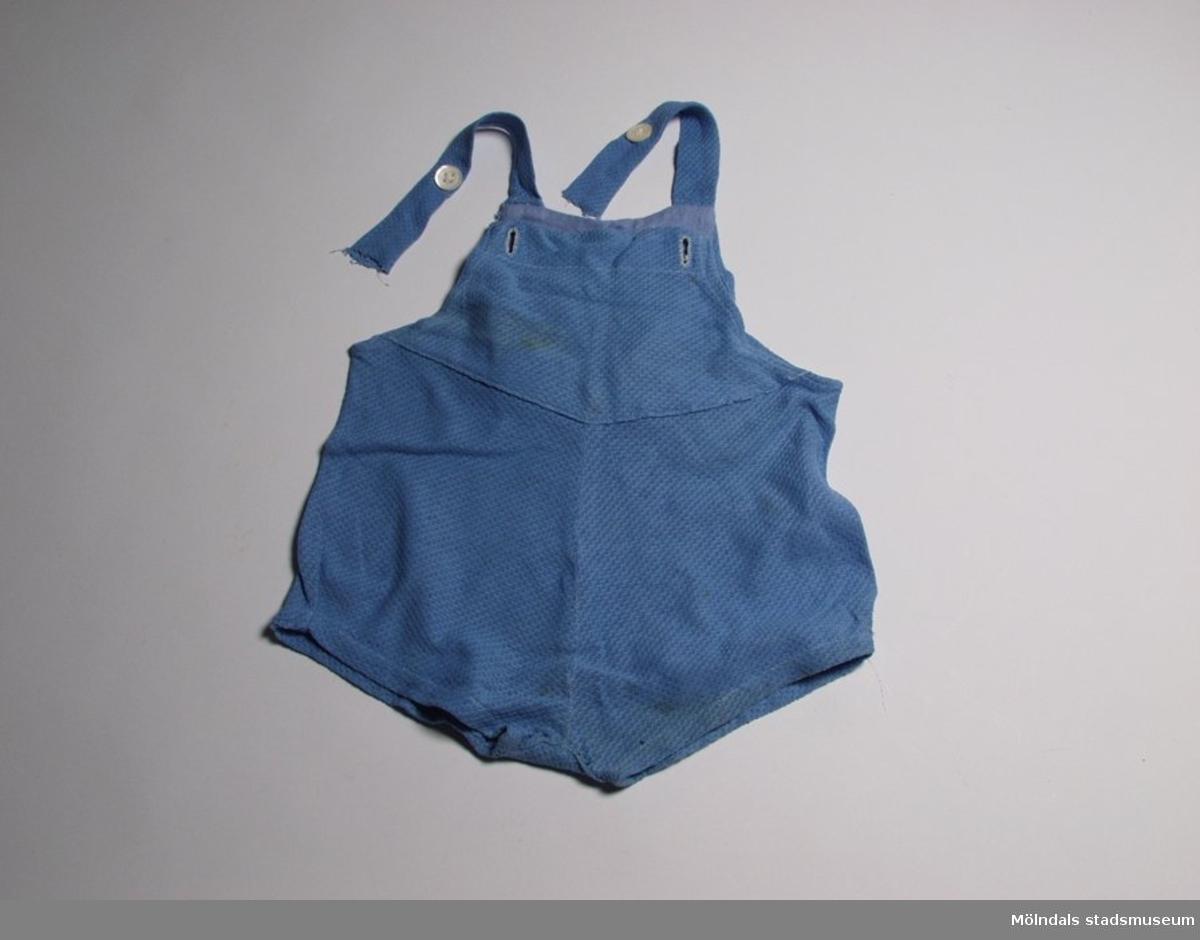 Hängslebyxa för barn med korta ben. Sydd i mellanblått tyg med lite struktur.