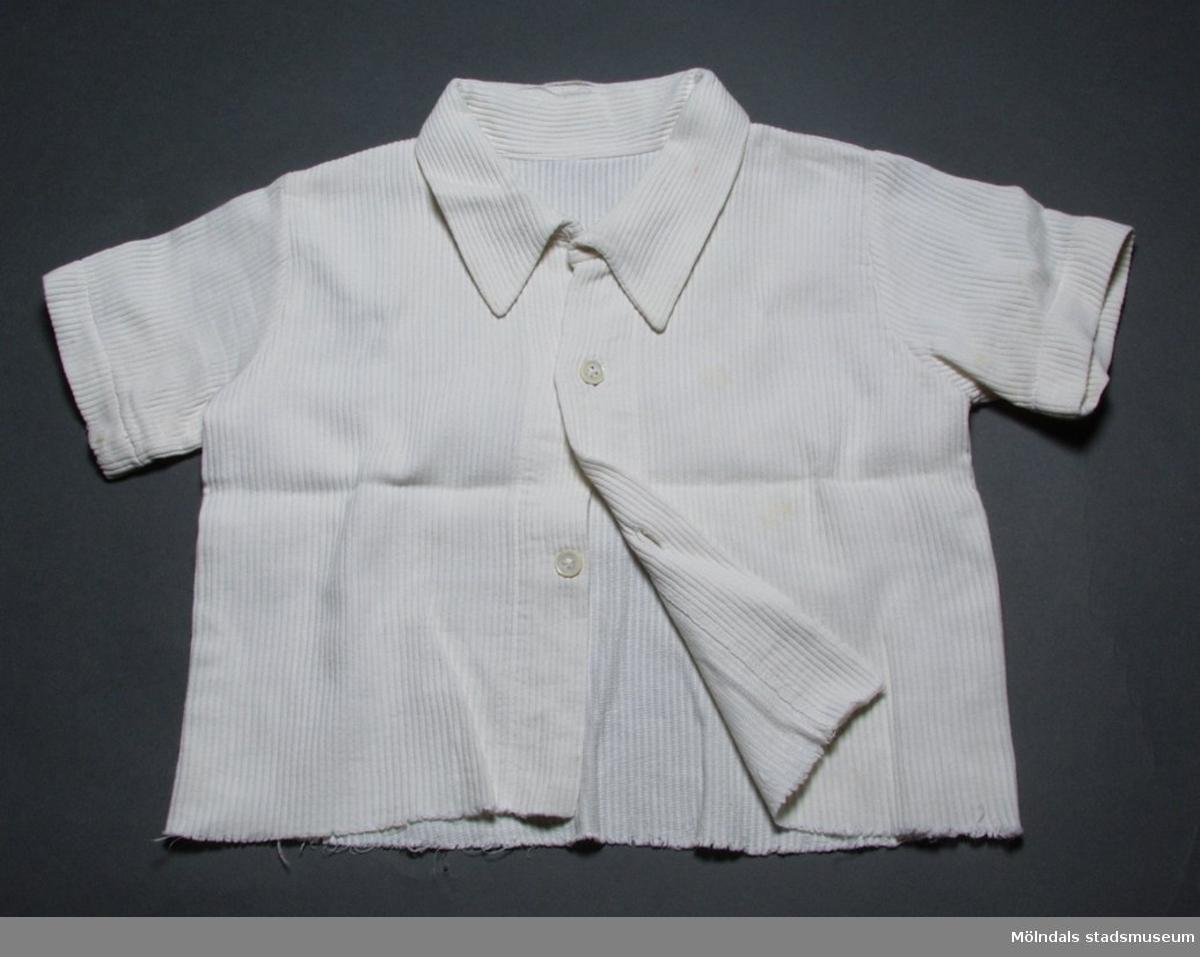 Barnskjorta i vit bomullstrikå med axelklaffar och kort ärm.