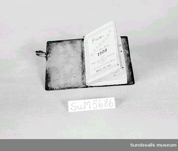 Fickkalender för år 1900 med pärmar i metall med graverat mönster. Kalendern är utgiven av P.A. Norstedt & Söners förlag, Stockholm. Tryckt hos Kungliga Boktryckeriet 1899. Pris 15 öre.