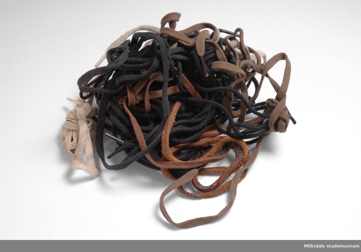 14 par oanvända skoband (8 par svarta och 6 par bruna) av olika fabrikat.Hittade i städskåpet i torpet som givaren hade köpt.
