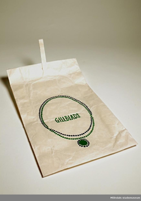 Vit papperspåse från varuhuset Gillblads i Göteborg. Tvåfärgade med logotype och ett halsband i grönt och blått.