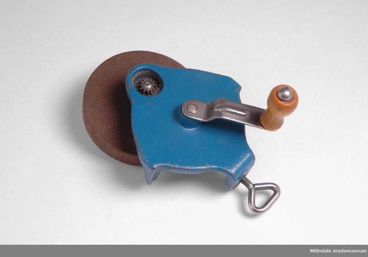 """Slipsten att fästa med skruv på bänkskiva. Vevkonstruktion av kugghjul, vevknopp av trä.Redskap och verktyg kommer från Lindströms snickeri (Gamla Riksvägen 81, Ekebacken). Här byggde John Lindström från Lindome ett boningshus och snickeriverkstad 1928. Han öppnade ett snickeri som specialiserade sig på köksbord Borden levererades till en grossist i Göteborg. Som mest tillverkades 50-60 bord i veckan. Borden hade ben av björk och resten var av furu. Han gjorde även andra möbler på beställning. Till hjälp hade John ett par anställda.De sista åren gjordes mest renoveringar och reparationer, medan det """"begav sig"""" de mest aktiva åren tillverkades bord av alla de slag."""