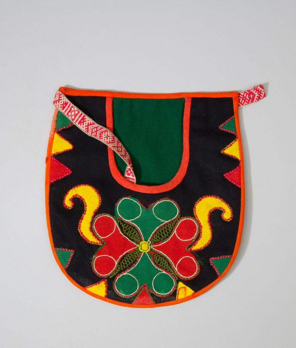 Kjolsäck till dräkt för kvinna från Leksands socken, Dalarna. Modell med u-formad öppning för handen. Tillverkad av svart ylletyg med applikationer av tunna ylletyger i rött, grönt och gult, fastsydda med ullgarn: läggsöm. Centralt placerat hjärtmotiv med slingor och trekanter på sidorna. Sparsamt broderi vid mittmotivet: flätsöm och stjälksöm, sydda med grönt och vitt bomullsgarn. Framstycket fodrat med svart tyg, fabriksvävt. Kantning runtom med rött diagonalvävt band. Grönt kläde i öppningens spegel. Bakstycke av svart kläde. Midjeband fabriksvävt, med plockat mönster i rött på vit botten med hake och trådträns.